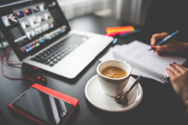 Creative professional desktop with laptop and coffee