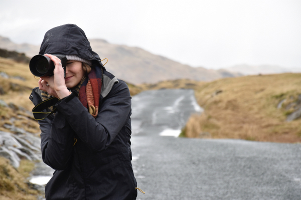 Female photographer on a road taking a photo