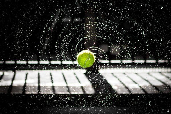 Tennis ball spinning with water droplets in symmetrical pattern