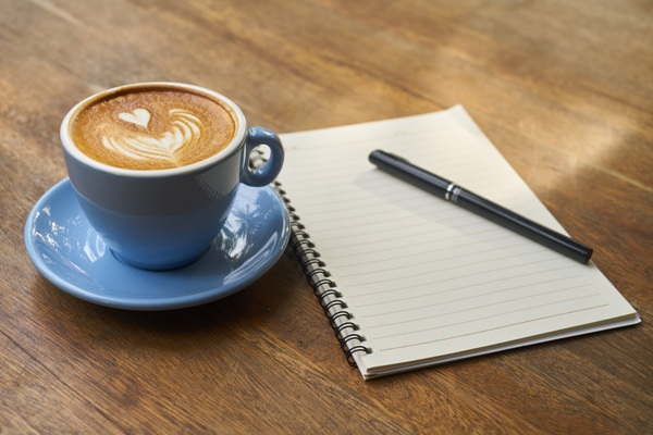 Coffee with heart in foam on desk next to notebook and pen