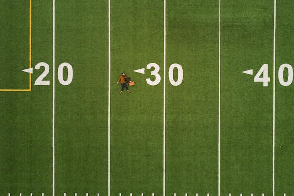 man lying on football field